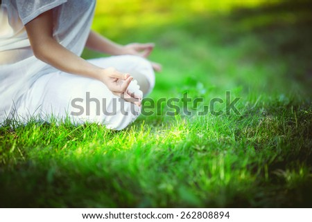 Woman in lotus pose outdoors - stock photo