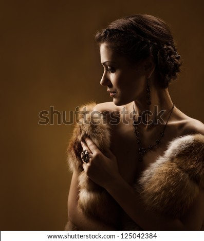 Woman in luxury fur coat. Vintage style. Brown background. - stock photo