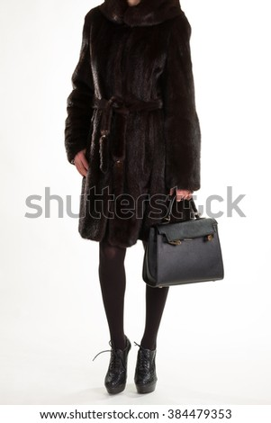 Woman in luxury furcoat. Brown furcoat and black purse. Woman's luxury outfit. Expensive garment in boutique.