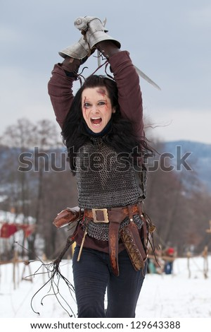 Woman in medieval clothes with a sword - stock photo