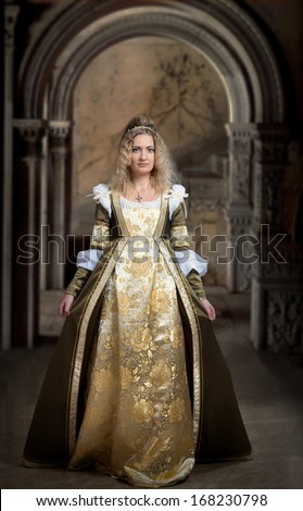 Woman in medieval dress, antique interior background - stock photo