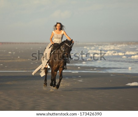 woman in medieval dress riding arabian horse on beach - stock photo