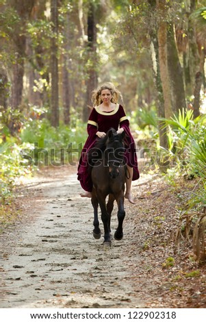 woman in medieval dress riding galloping horse through forest - stock photo
