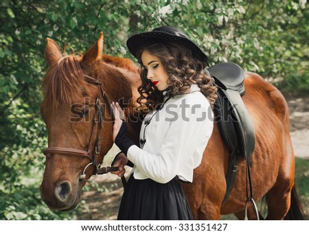 Woman in medieval dress standing with horse near forest and touching to horse face