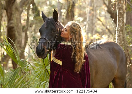 woman in medieval dress with horse in forest - stock photo