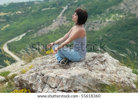 Woman in meditation, relaxing on the rock - stock photo