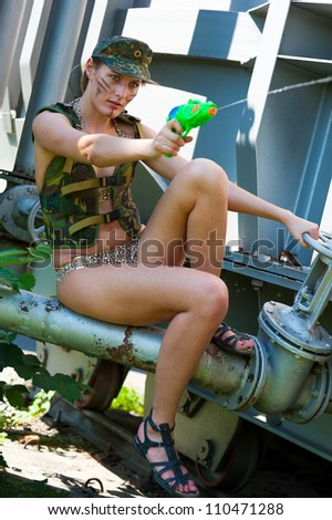 Woman in military camouflage shoots from a water pistol on the industrial background
