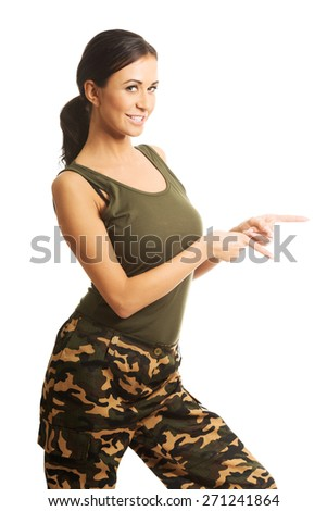 Woman in military clothes pointing to the left. - stock photo