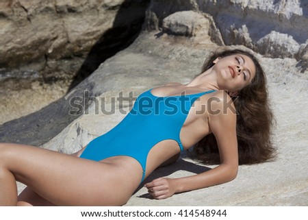 Woman in modish swimsuit sunbathing at the rocky beach with provocative face expression.