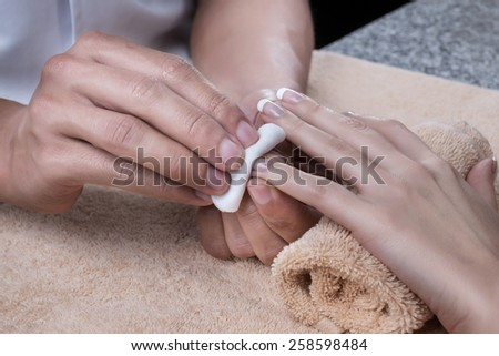 Woman in nail salon is receiving manicure by beautician. Nail polish removal