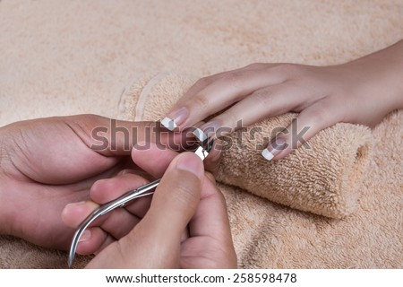 Woman in nail salon is receiving manicure by beautician. Trimming the cuticle