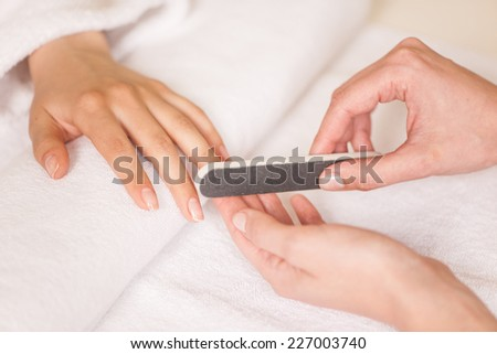 Woman in nail salon receiving manicure by beautician. closeup image of hands polishing fingers on towel - stock photo