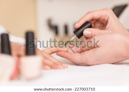 Woman in nail salon receiving manicure by beautician. Woman getting manicure at beauty salon  - stock photo