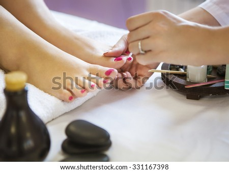 Woman in nail salon receiving pedicure by beautician. Close up of female hand resting on white towel - stock photo