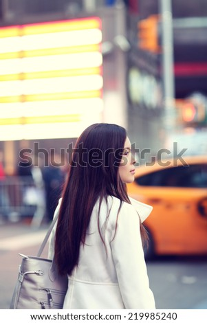 Woman in New York City Manhattan. Young urban professional business woman walking in street wearing coat downtown with yellow taxi cabs in background. Multiracial Asian Caucasian businesswoman in USA. - stock photo