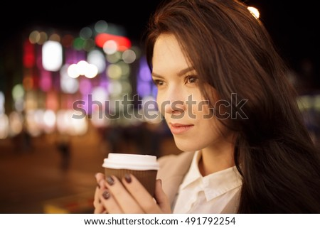 Woman in night city keeping coffee cup and enjoying it aroma