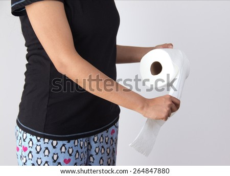 Woman in night pants tearing tissue from toilet paper roll - stock photo