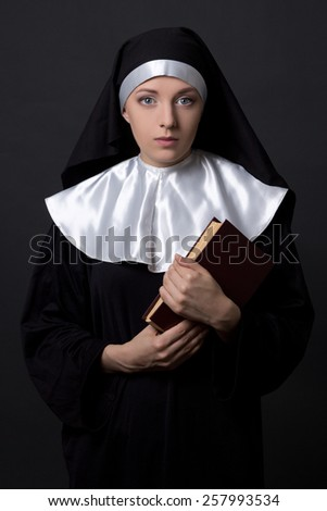 woman in nun veil with book over grey background - stock photo