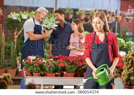 Woman in nursery shop watering plants and flowers with watering can - stock photo