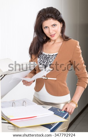 woman in office near the copier with documents - stock photo