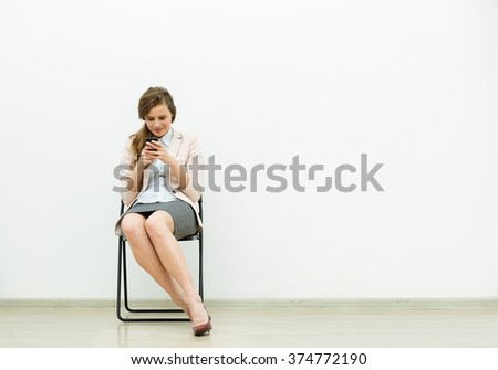 woman in office outfit sitting in a chair with and talking relaxed at cellphone - stock photo