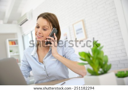 Woman in office talking on mobile phone - stock photo