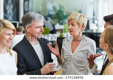 Woman in office telling joke to her team and her colleagues laughing - stock photo