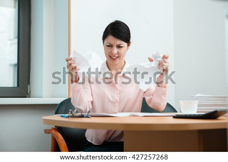 Woman in office with crumpled paper. - stock photo