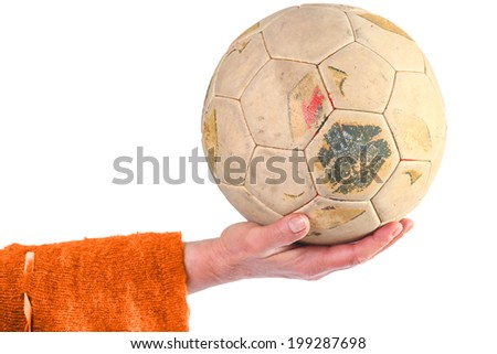 Woman in orange cardigan holding old and weathered soccer ball in hand - stock photo