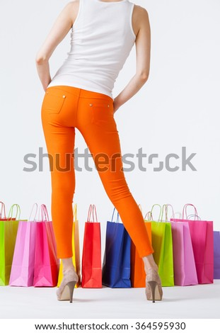 Woman in orange pants and multicolored shopping bags, shopping concept
