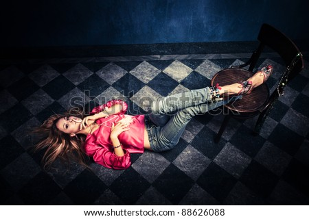woman in oriental shirt and shoes lie on floor show sign of  silence with finger on lips - stock photo