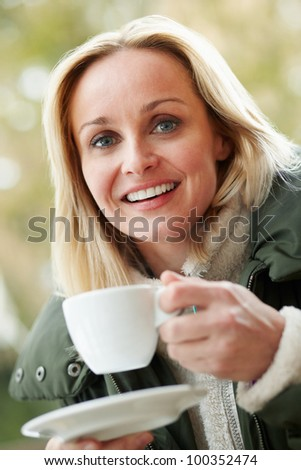 Woman In Outdoor Cafe With Hot Drink  Wearing Winter Clothes - stock photo