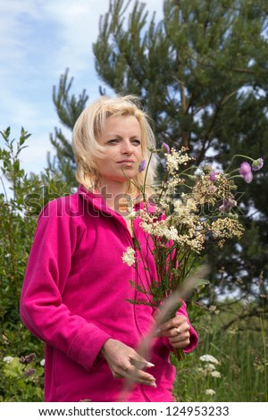 Woman in outdoors cutting wild flowers