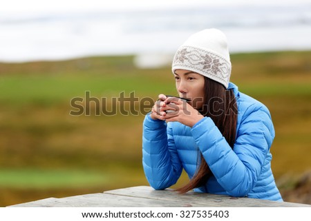 Woman in outdoors drinking coffee from thermos cup sitting outside wearing warm down jacket and knit hat. Pretty young mixed race Asian Chinese Caucasian woman living active lifestyle.