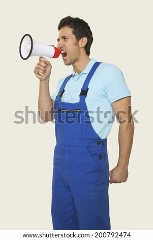 Woman in overall shouting through megaphone waist up