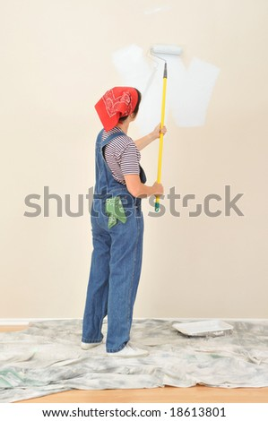 Woman in overalls using paint roller on extension pole painting wall. Viewed form behind the woman is unrecognizable. - stock photo