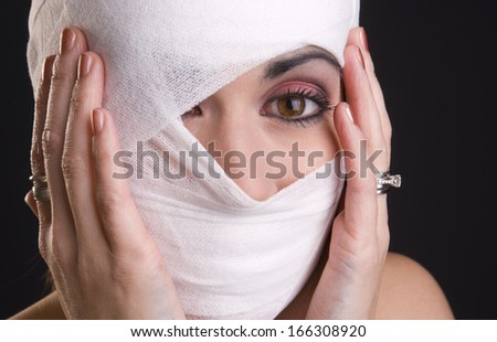 Woman in pain holds her head that has been injured and wrapped in first aid gauze - stock photo