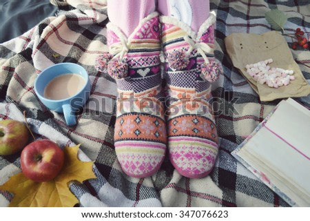 woman in pajamas and ugg boots reading a book in bed.Woman having breakfast in bed and reading