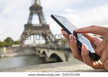 Woman in Paris using her cell phone in front of Eiffel Tower, seine bridge background, message sms e-mail - stock photo