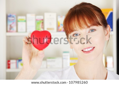 Woman in pharmacist uniform is standing in drugstore and showing red small heart, symbol of cardiology. - stock photo