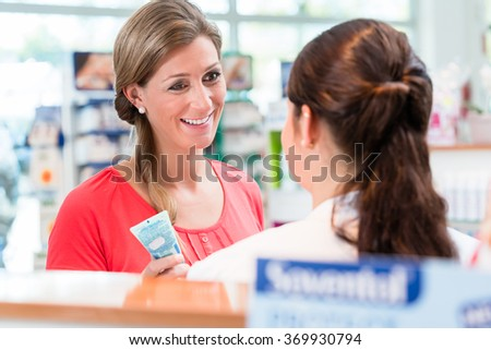 Woman in pharmacy being counseled by sales lady - stock photo