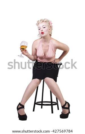 Woman in pin-up dress drinking on a chair- Isolated White Background - stock photo