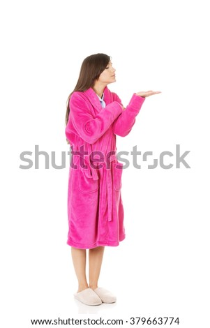 Woman in pink bathrobe showing empty palm. - stock photo