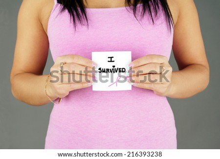 Woman in pink holding cancer survivor text with ribbon