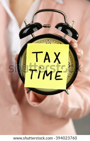 Woman in pink suit holding alarm with tax time inscription, close up - stock photo