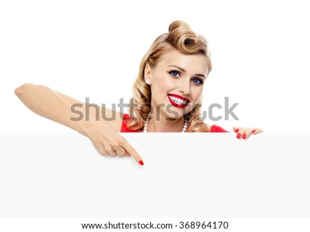 Woman in pinup style dress showing blank signboard with copyspace area for slogan or text, isolated on white background. Caucasian blond model posing in retro fashion and vintage concept studio shoot.