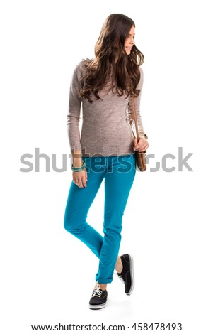 Woman in plain beige sweater. Bright turquoise pants. Trendy slim-fit trousers. Nice outfit with accessories.
