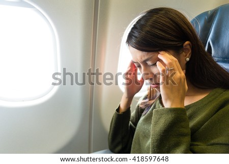 Woman in plane suffer from airsick with stress headache - stock photo