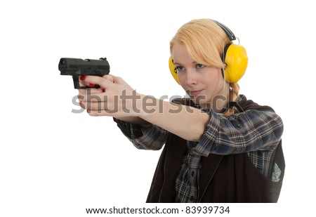 woman in protective receivers aiming a pistol at shooting range