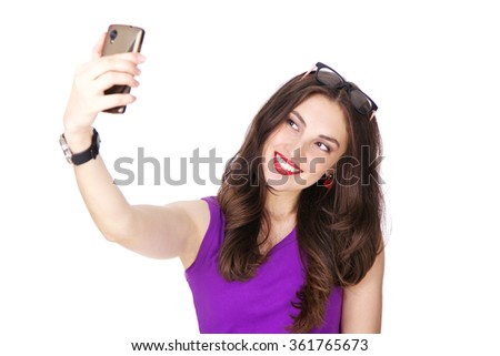 Woman in purple tank top happy smiling and making a selfie on her mobile. Fit and athletic Caucasian brunette girl posing on white background.